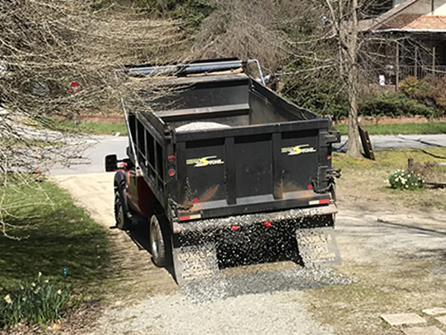 Just a few inches of gravel at a time.- Tailgate Spreading Gravel at the Cabin
