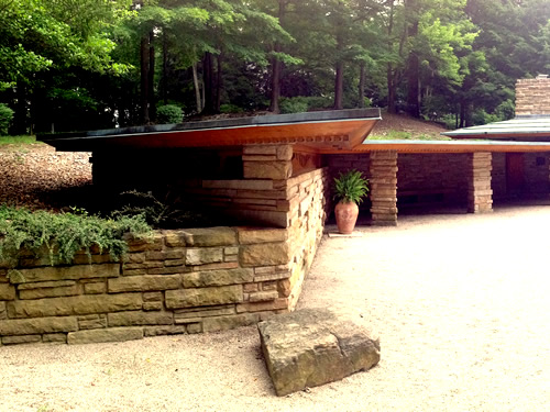 A flat-roofed carport and studio are built into the hill on one side of Kentuck Knob. Portion of photo by Kafziel