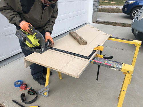 The square is clamped down to make a guide for the saw.