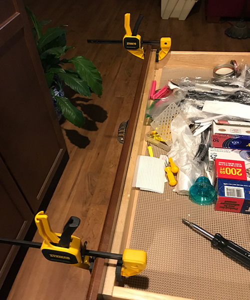 Clamping on the drawer front to mark the dents for the screw heads