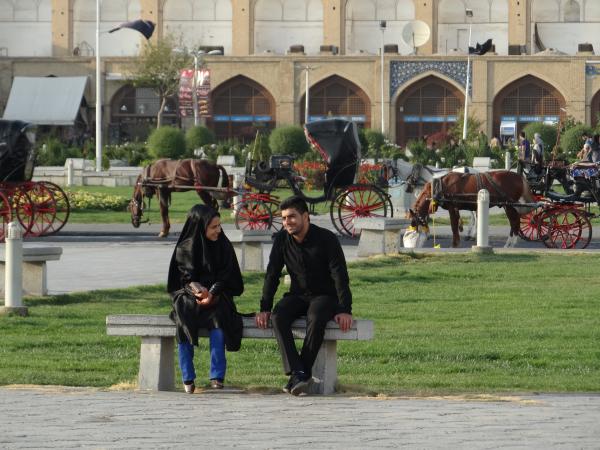 Um casal conversando normalmente na principal praça de Isfahan