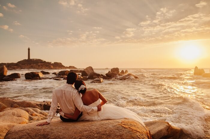 shutterstock_552748282-honeymoon-couple-relax-on-sunset-beach.-Sea-view-with-lighthouse-in-Vietnam