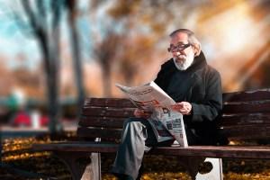 A gentleman in a park, reading newspaper
