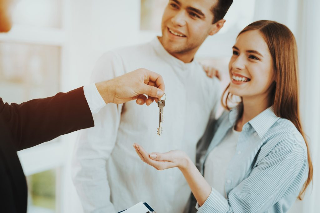 Realtor Is Giving A House Key To Young Couple. Bright Office. Ke