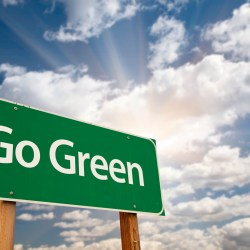 Go Green on road sign with blue sky and sunshine for 9 Green Property Management Initiatives for 2019