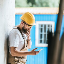 Construction Worker On Phone And Smoking For 6 Tips to Avoid Low Quality Contractors Blog