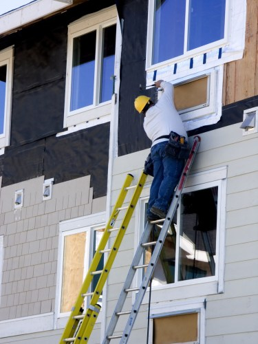 Man Installing New Commercial Siding As An Example of Great CapEx Projects for Commercial Properties