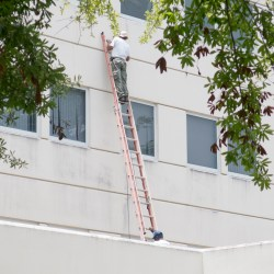 Worker On Ladder Performing Expensive Commercial Property Repairs
