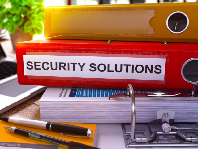 Security Solutions On Red Binder On Multifamily Property Manager's Desk