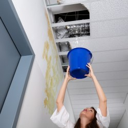 Woman Holding Bucket To Ceiling Because The Commercial Roof Is Leaking In Hallway