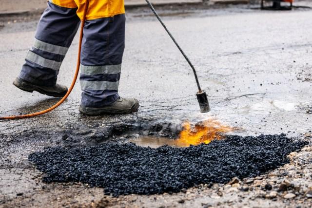Worker Performing Commercial Pothole Repair Services Using Hot Mix Asphalt