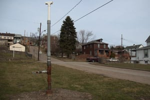 Vents like the one pictured in the foreground have been installed throughout Versailles, Pa., so gas from abandoned wells can be directed away from homes. (Nicholas Kusnetz /ProPublica)