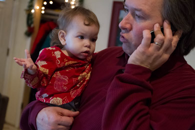 Willie Rembis talks on the phone while holding his daughter Cora. (Jeffrey Sauger for ProPublica)