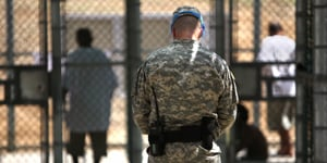 In this pool photo, reviewed by the U.S. military, and shot through glass, a guard watches over Guantanamo detainees inside the exercise yard at Camp 5 detention facility at Guantanamo Bay U.S. Naval Base, Cuba, on May 31, 2009. (Brennan Linsley/AFP/Getty Images)