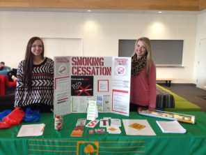 Photo courtesy of Molly Martin | Parkland College Students Hayley Briggs (left) and Ashlyn Gregory (right) stand at a smoking cessation table in Parkland's cafeteria.