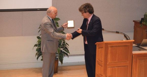 Photo by Tom Warner |  Tamer Basar, director of the University of Illinois' Center for Advanced Study, presents Jonathan Sweedler with an appreciation plaque after his lecture at the Spurlock Musuem's Knight Auditorium on Oct. 11.