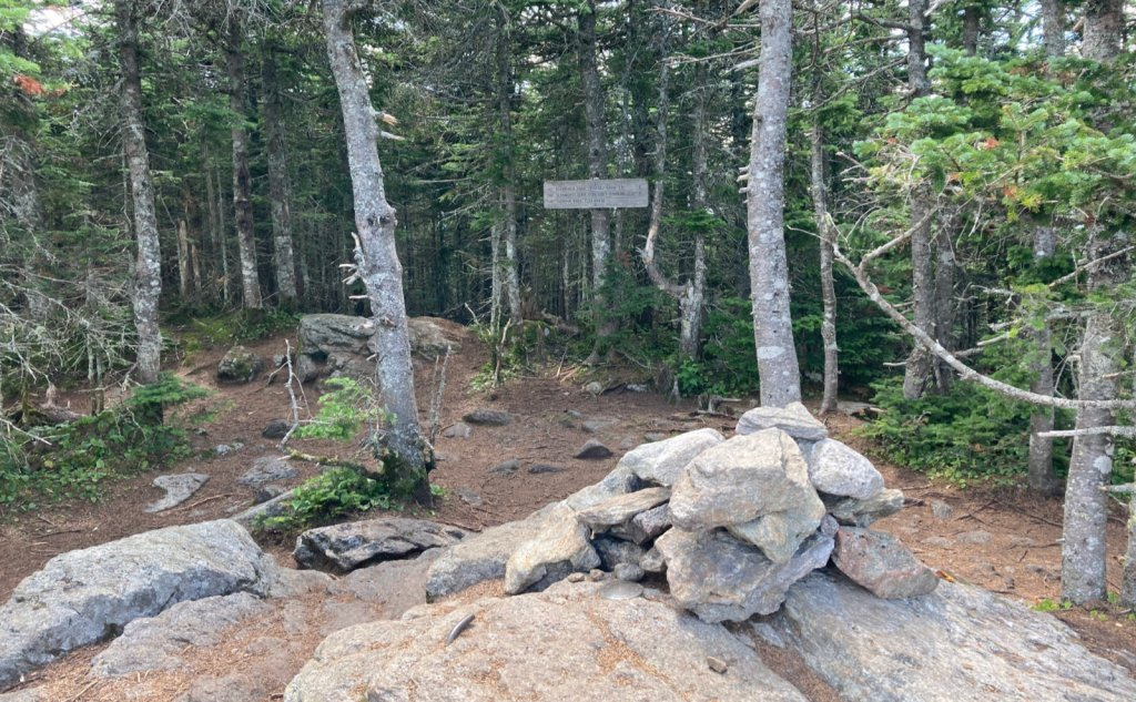 Summit cairn and sign.