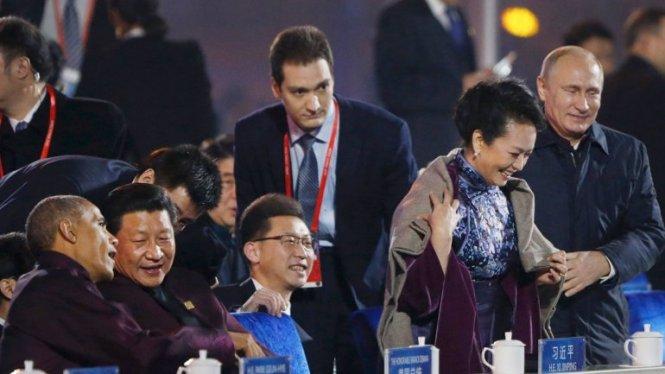 El presidente Putin cubre a la mujer del presidente chino con una manta.