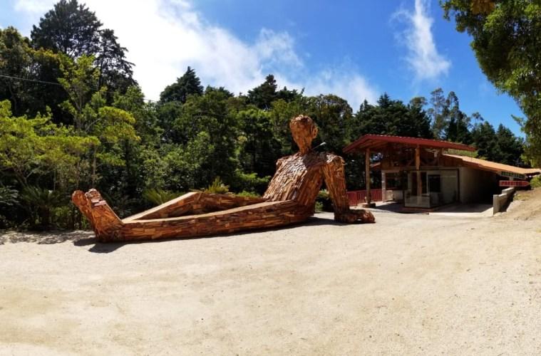 """Eine Riesenskulptur aus Holz und recyceltem Metall """"chillt"""" in der Sonne Costa Ricas vor dem Selina Hotel in Monteverde."""