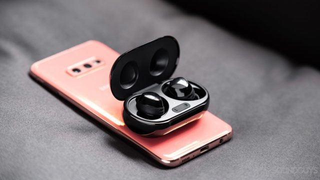 A photo of the real Samsung Galaxy Buds Plus wireless earbuds with PowerShare wireless on a Samsung Galaxy S10e.