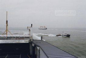 Een Belgische redeboot baant zich een weg over de Westerschelde, vastgelegd tussen twee PSD-veerboten.