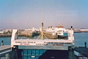 De veerboot Koningin Beatrix verlaat de fuik van Vlissingen en zet koers naar Breskens. Naast de fuik ligt de veerboot Prins Johan Friso. Op de achtergrond zien we het NS-station Vlissingen.