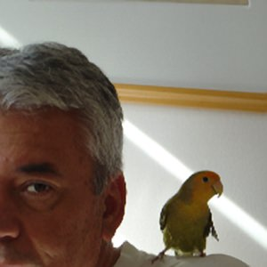 Pseudomyxoma survivor Milton with his pet bird on his shoulder