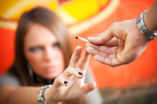 cropped view of two young adults smoking a joint