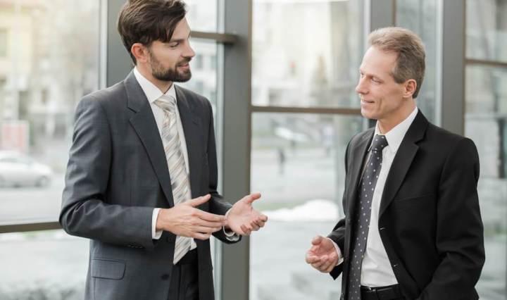 Gerente de la compañía hablando con empleado, dando le retroalimentación de las tareas desempeñadas en su cargo