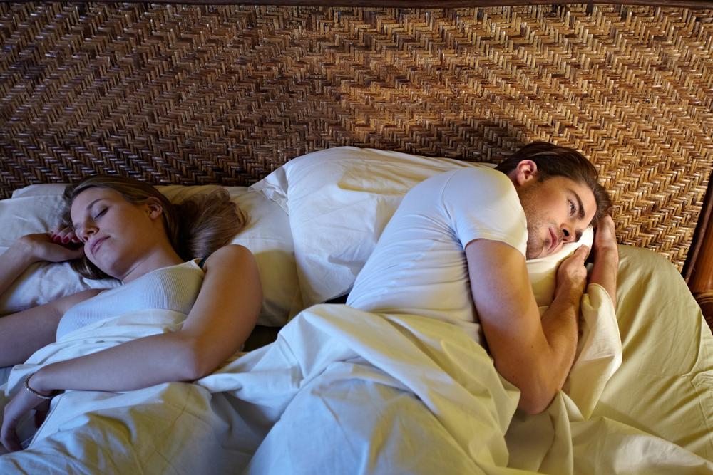 Joven tumbado en la cama al lado de su pareja pero sufriendo de insomnio