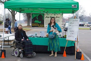 Man in power wheelchair and woman holding a small black and white dog smile under a green canopy and in front of a decorated table holding educational materials. A dry-erase board on an easel is on the right and a PSDP banner is suspended in the background.