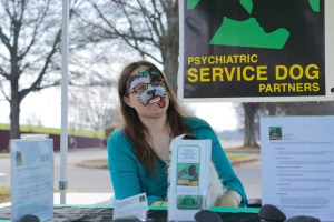 Surrounded by a PSDP banner and assorted educational materials laid out tastefully on a table, a woman with long brown hair laughs with smiling eyes at the camera. Notably, she has a small black and white dog in her lap, occluded by flyers in an acrylic stand. Even more notably, her face is painted in a silly, stylized way so that she looks like her dog!