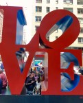 "A young man smiles as he crouches with his Miniature American Shepherd inside a giant red and blue ""LOVE"" statue in New York City. The ""L"" and ""O"" are on top of the ""V"" and ""E"" and the whole statue is around 25 feet tall."