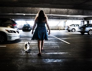 In a parking garage, the silhouette of a woman walking away from the viewer with a small dog strongly contrasts against her surroundings.
