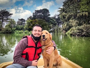 Colin is sitting in a rowboat with a golden retriever, Lyla, in a green lagoon, facing the camera. He is a young man and has dark brown hair, light skin, and is wearing a red life jacket, jeans, a black mask under his chin, and a burgundy shirt. Lyla has a medium gold coat. Lyla and Colin are both smiling with eyes closed in happiness while Colin puts his arm around Lyla.