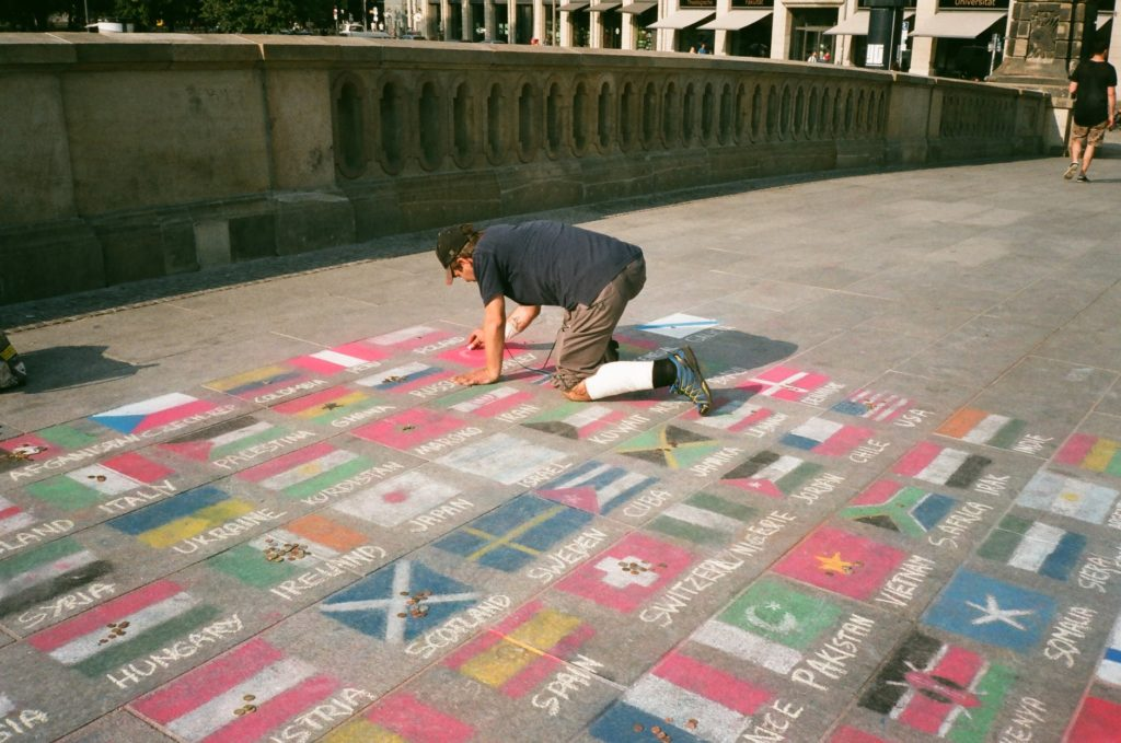 man drawing national flags