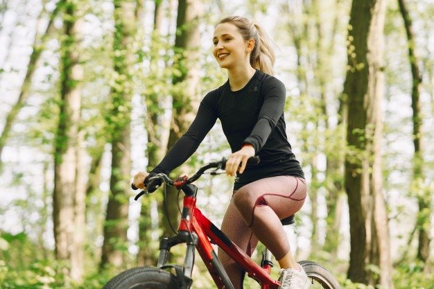 young woman biking in the woods