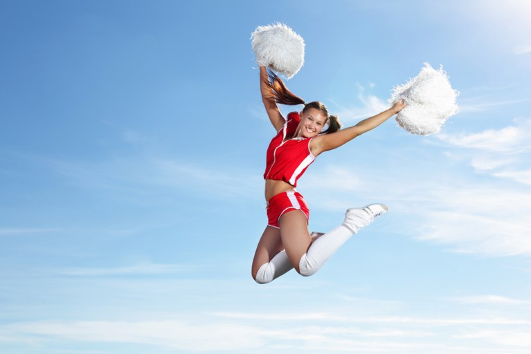 Cheerleader jumping high in the air to raise crowd's mood