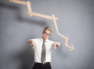Upset businessman in front of descending graph.