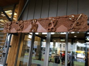 The carved lintel adorns the entrance to Te Pātaka Kōrero o Te Hau Kapua. The five carved figures on the pare capture the history and individual styles of Te Kawerau ā Maki, Ngāti Whātua o Ōrākei, Ngai Tai ki Tāmaki, Ngāti Maru and Ngāti Paoa.