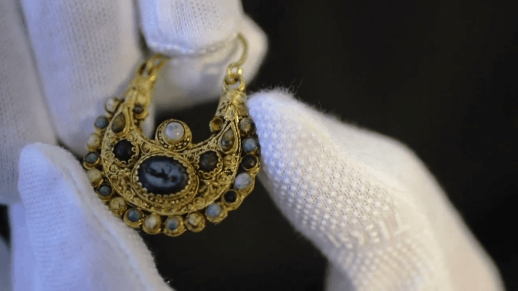 A large gold earring studded with multiple gemstones, with a large etched blue gemstone in the centre, held by a person wearing white gloves.