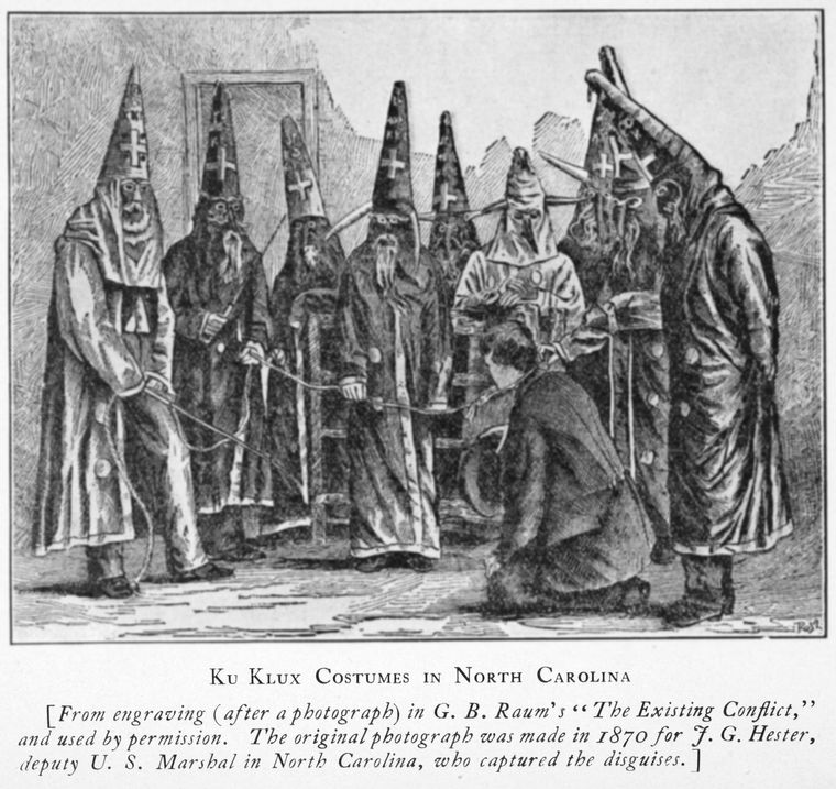 A black and white engraving of a group of men in robes with tall hoods surround another man in a suit on his knees.