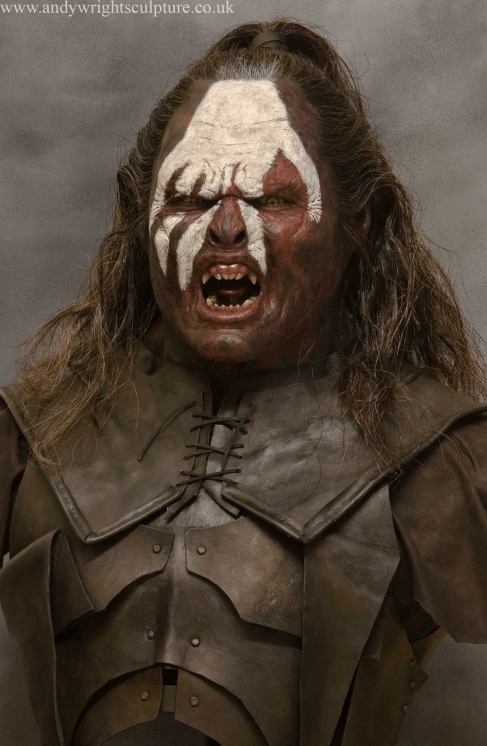 Lurtz, an Uruk-hai character from Peter Jackson's The Lord of the Rings films wearing beaten metal armor, a white handprint on his face, and a menacing expression