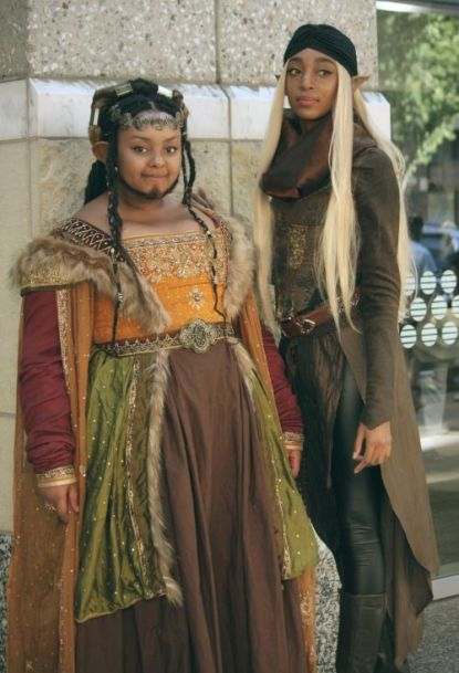 Two black women, one dressed as an elf and another dressed as a dwarf.