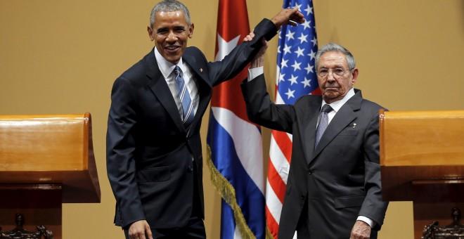 El presidente de Cuba, Raúl Castro, levanta el brazo de Obama tras la conferencia de prensa en el Palacio de la Revolución, en La Habana.- REUTERS