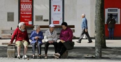 Varios pensionistas sentados en un banco cerca de una oficina bancaria en la localidad burgalesa de Briviesca. AFP / César Manso