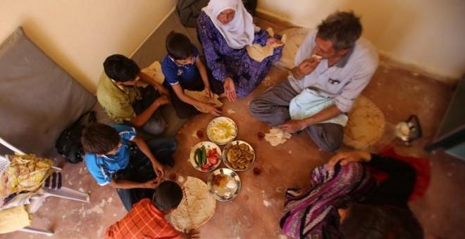 Una familia siria que tuvo que huir de la ciudad de Daraya se reúne para desayunar en una pequeña habitación a las afueras de damasco. - AFP