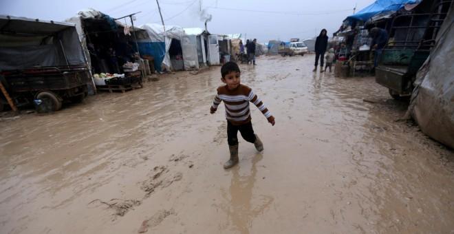 Un niño anda entre el barro en un campamento de desplazados sirios junto a la frontera con Turquía. - REUTERS