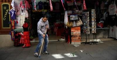 El empleado de una tienda de objetos turísticos del centro de Madrid barre la acera. REUTERS/Susana Vera