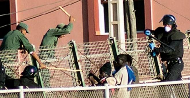 Agentes de la Guardia Civil y las fuerzas auxiliares marroquíes tratan de impedir que que varias personas migrantes salten la valla de Melilla.- CAMINANDO FRONTERAS